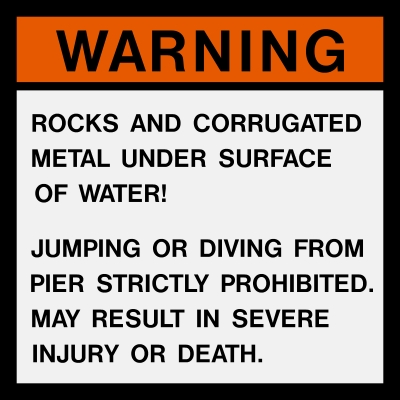 This is a warning sign located at the beach explaining hazards, and warning swimmers not to jump or dive from the pier into Lake Michigan.